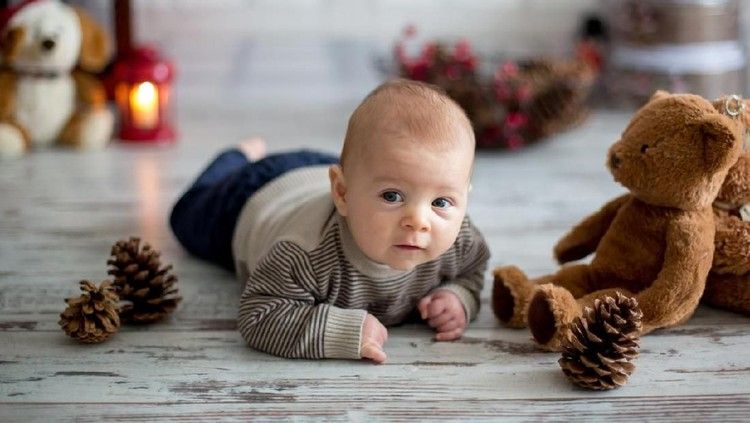 Christmas portrait of cute little newborn baby boy, dressed in christmas clothes and wearing santa hat, studio shot, winter time