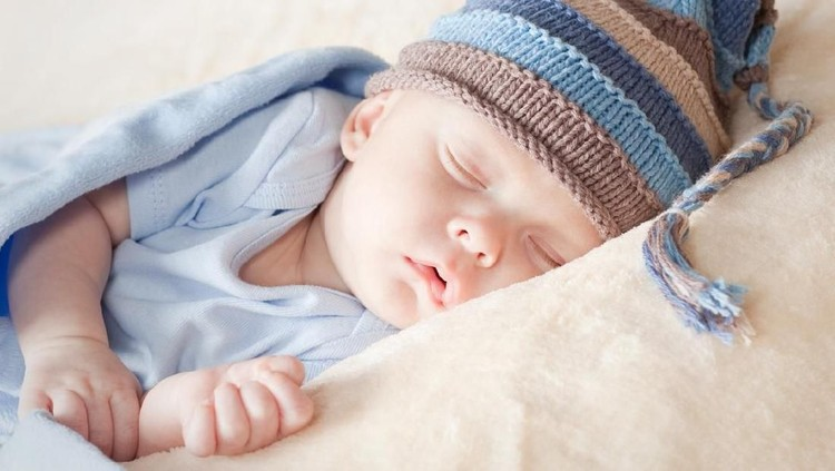 A 12 day old newborn baby boy sleeping on a beige flokati rug and swaddled in a gauzy light blue wrap.