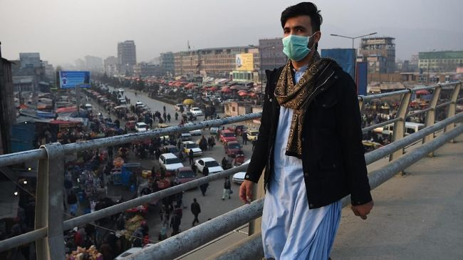 In this photograph taken on January 16, 2019, an Afghan resident wearing a face mask walks along an overpass amid heavy smog conditions in Afghanistan's capital Kabul. - Kabul residents have long run the gauntlet of suicide attacks and bombs. This winter, however, they face another deadly threat: air pollution. For weeks a thick layer of toxic smog has blanketed the sprawling city as cold air traps pollution caused by people burning coal, wood, car tyres and even garbage to stay warm. (Photo by WAKIL KOHSAR / AFP) / TO GO WITH: PHOTOESSAY - AFGHANISTAN-POLLUTION