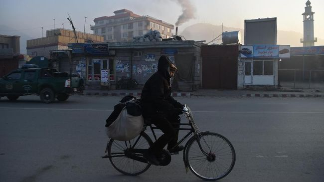 In this photograph taken on January 17, 2019, an Afghan resident rides a bicycle along a road amid heavy smog conditions in Afghanistan's capital Kabul. - Kabul residents have long run the gauntlet of suicide attacks and bombs. This winter, however, they face another deadly threat: air pollution. For weeks a thick layer of toxic smog has blanketed the sprawling city as cold air traps pollution caused by people burning coal, wood, car tyres and even garbage to stay warm. (Photo by WAKIL KOHSAR / AFP) / TO GO WITH: PHOTOESSAY - AFGHANISTAN-POLLUTION