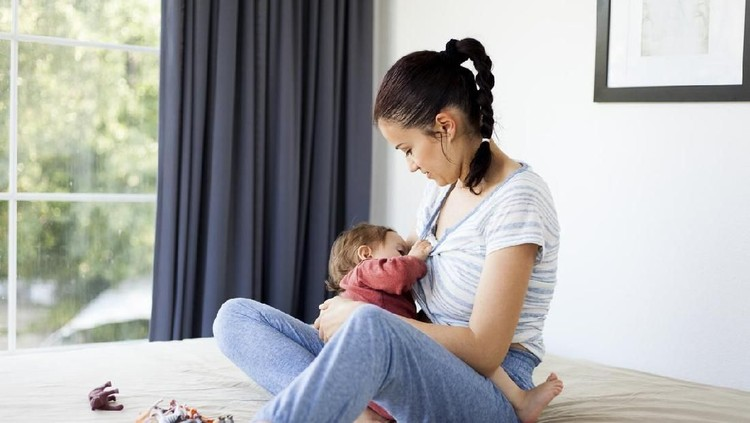 Mom breastfeeds her baby at home