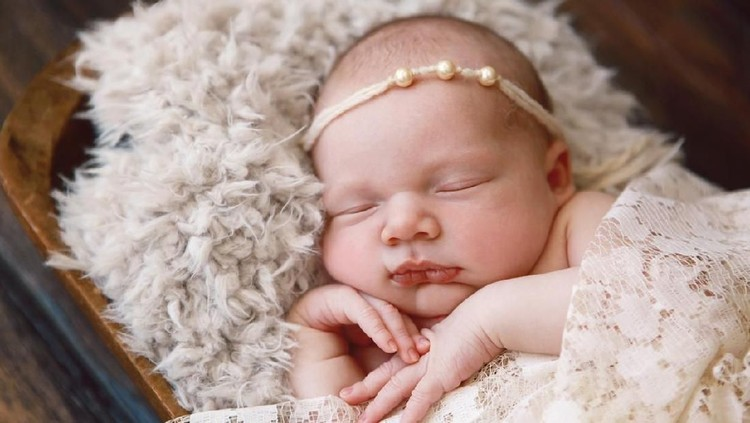 A beautiful newborn baby girl sleeps soundly in an antique wooden bowl.