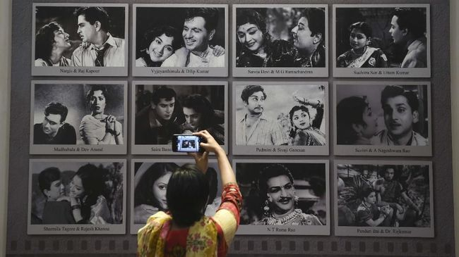 In this picture taken on January 22, 2019, a visitor takes a picture of a display with images of former Indian movie actors at the National Museum of Indian Cinema (NMIC), the country's first museum showcasing the history of its film industry, in Mumbai. - From silent black-and-white films to colourful blockbusters bursting with song and dance, a new museum tracing the evolution of Indian cinema has opened in the home of Bollywood. Costing 1.4 billion rupees (19.6 million USD), India's first national film museum is spread across a stylish 19th-century bungalow and a modern five-storey glass structure in south Mumbai. (Photo by PUNIT PARANJPE / AFP) / TO GO WITH AFP STORY INDIA-ENTERTAINMENT-FILM-BOLLYWOOD-HISTORY-MUSEUM,FOCUS BY UDITA JHUNJHUNWALA AND PETER HUTCHISON