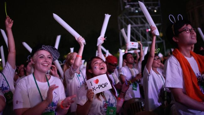 In a photo taken on August 4, 2015 fans cheer during a public K-Pop concert in Seoul. The concert, which was free for foreigners, was organised by the Korea Tourism Office in the wake of the country announcing an end to the recent MERS outbreak which took a heavy toll on the national economy, stifling consumer spending and devastating the tourist sector. Local businesses including shopping malls, restaurants and cinemas reported a sharp drop in sales as people shunned public venues with large crowds. AFP PHOTO (Photo by ED JONES / AFP)
