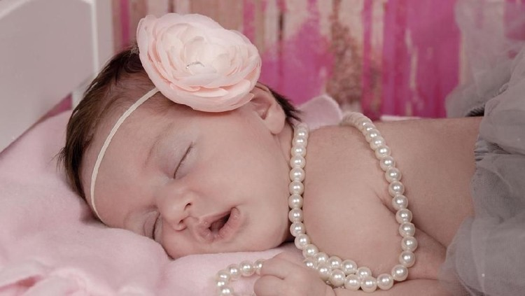 Closeup of beautiful one week old newborn girl sleeping with a gorgeous pink flowered headband. She is also wearing pearls and a gray tutu.