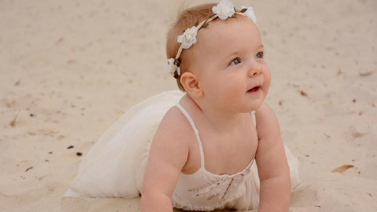 Cute baby crawling in the sand