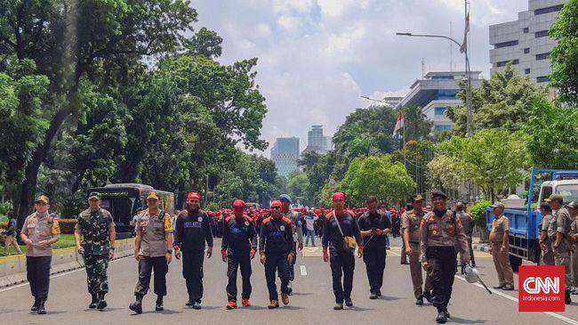 Polisi mengalihkan sejumlah ruas jalan saat kelompok buruh dan mahasiswa menggelar demo menolak omnibus law UU Cipta Kerja, Selasa (20/10).
