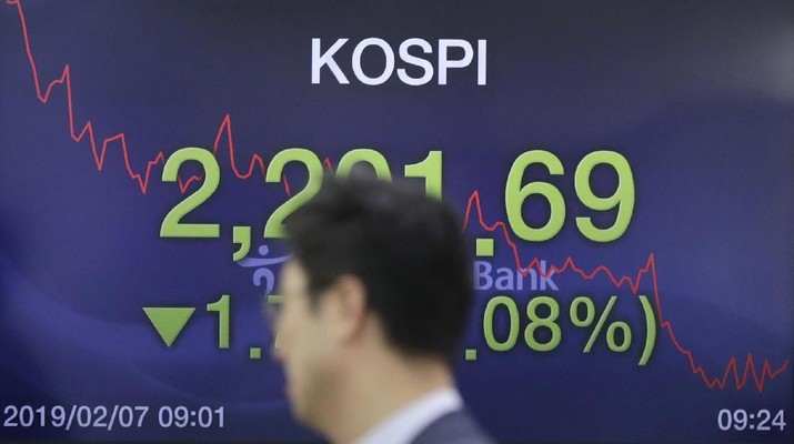 A currency trader walks by screens showing the Korea Composite Stock Price Index (KOSPI), left, and the foreign exchange rate between U.S. dollar and South Korean won at the foreign exchange dealing room in Seoul, South Korea, Thursday, Feb. 7, 2019. Asian shares were mostly higher Thursday on news that the Reserve Bank of Australia may cut interest rates, driving hopes that other central banks could come to the same conclusion. (AP Photo/Lee Jin-man) - PT Rifan