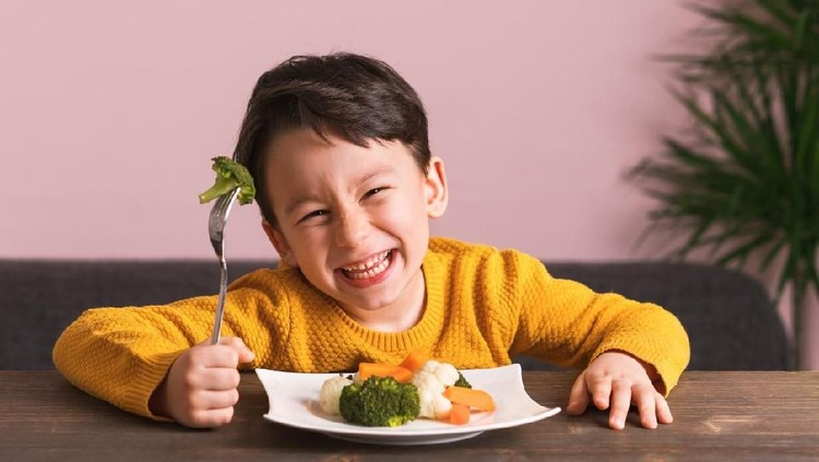 Little boy is enjoying his stir fry dinner and socialising with his family at home.