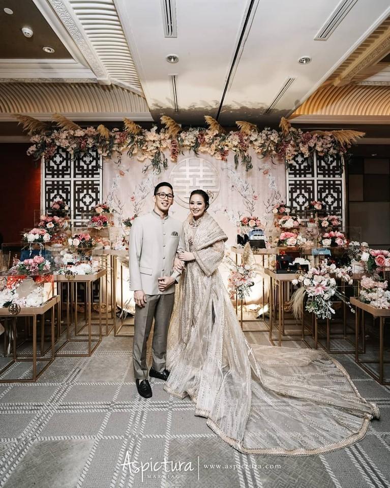 Yuanita Christiani dan Indra tampak serasi dalam balutan busana Tionghoa modern. Yuanita mengenakan gaun warna krem, serasi dengan Indra yang mengenakan setelan abu-abu terang.