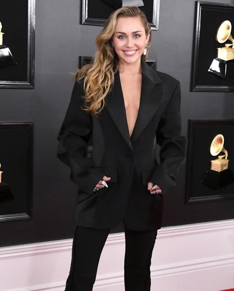 Miley Cyrus tampil sederhana dengan blazer dan celana hitam polos. Tampilan simpel Miley di Grammy Awards ini justru membuatnya semaki memesona.