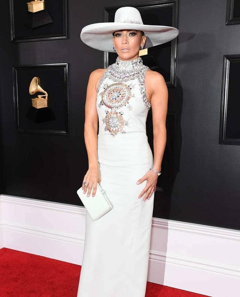 Jennifer Lopez tampil sempurna dengan balutan gaun putih panjang dengan detail yang glamour di bagian dadanya. Jlo juga semakin nyentrik dengan topi sombrero ala Mexico.