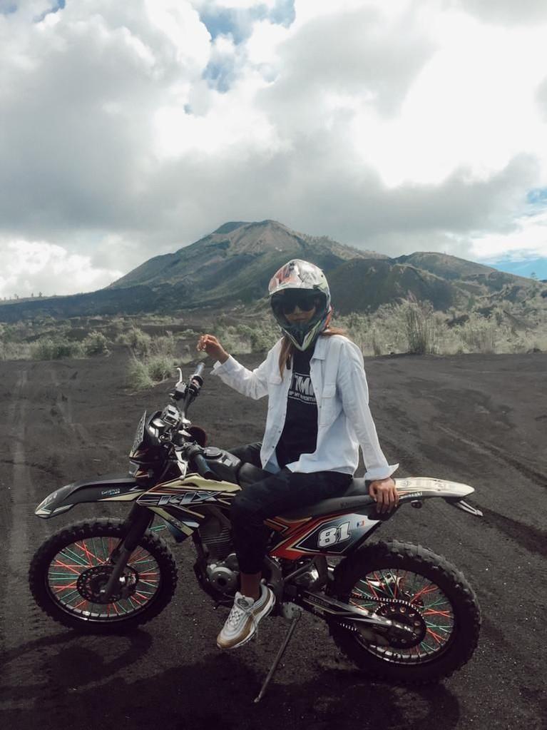 Maria naik motor trail di Black Lava Gunung Batur Bareng. Tak sendiri host cantik ini ditemani oleh para komunitas.