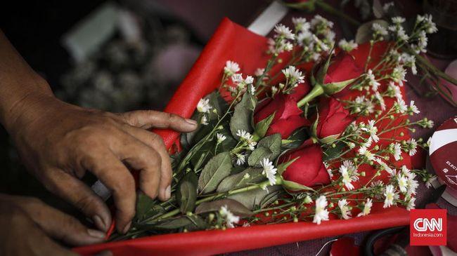 Pekerja merangkai bunga Mawar yang dijual di sebuah toko bunga di Pasar Kembang Cikini, Jakarta, 14 Februari 2019. Pada perayaan hari kasih sayang atau hari Valentine  hari ini harga bunga mawar naik hingga dua kali lipat. (CNN Indonesia/ Hesti Rika)