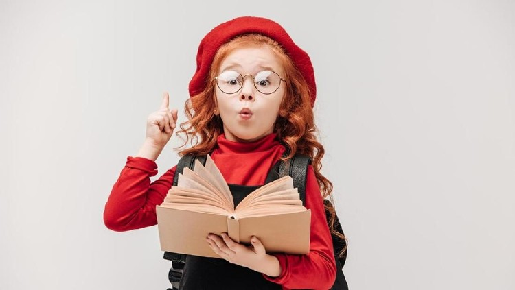 little schoolgirl having idea while reading book isolated on grey