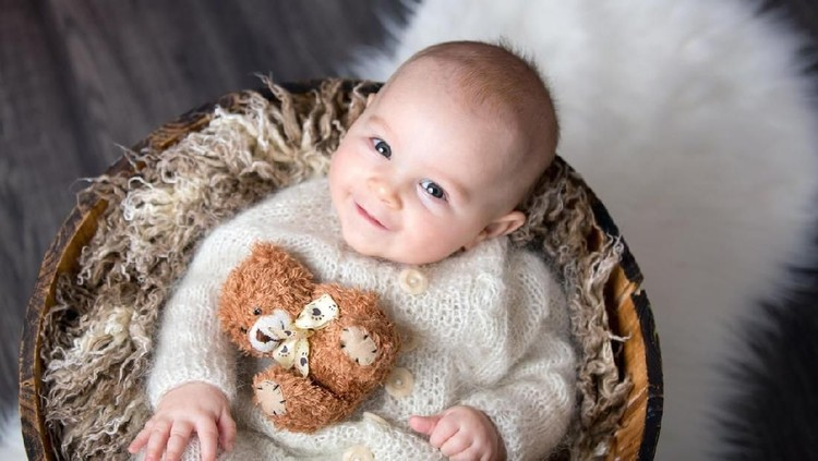 Cute little baby boy with handmade knitted cloths, playing with little teddy bear toy, smiling at camera