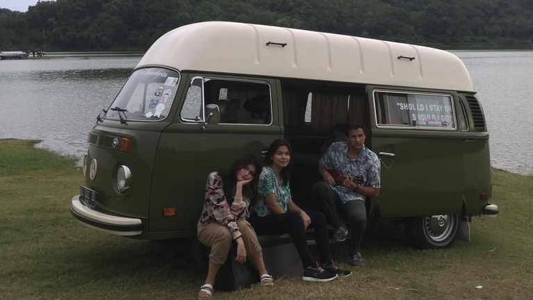 Para kru dan host Celebrity On Vacation bersantai di dalam mobil Van yang terparkir di pinggir danau yang teduh.