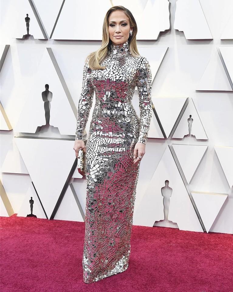 Jennifer Lopez datang dengan kostum yang terlihat dilapisi pecahan kaca berkilau berbentuk mosaik. Gaun ini merupakan karya dari desainer Tom Ford