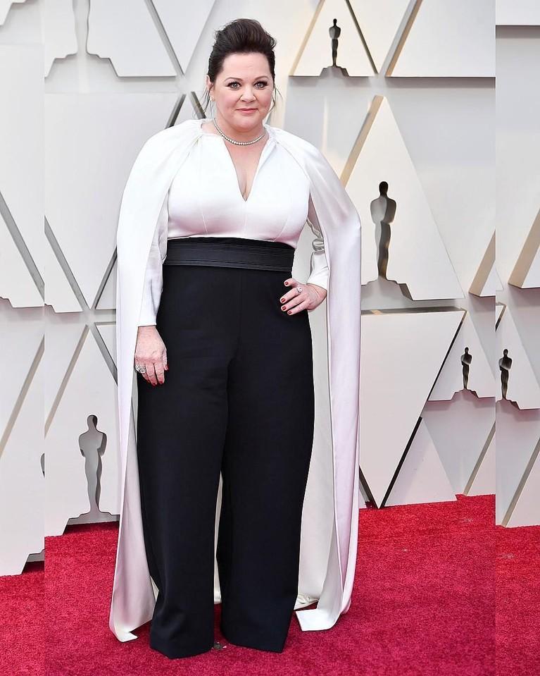 Di pergelaran Piala Oscars 2019,Melissa Mccarthy terlihat lucu dengan kostum besar mirip bajak laut ini. Perpaduan baju lengan panjang putih dan celana hitam lebar, unik.