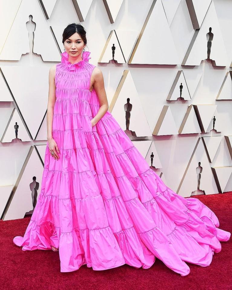 Gemma Chan tampil imut dengan mengenakan gaun seperti tiraiberwarna pink. Dengan bentuk renda-renda hingga ke bagian leher.