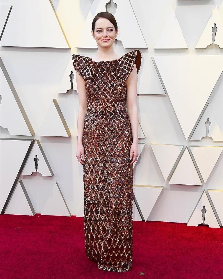 Emma Stone terlihat memakai gaun merah burgundi dengan tekstur seperti sarang madu lebah dengan bentuk tajam di bagian bahunya. Gaun ini keluaran rumah mode Louis Vuitton.