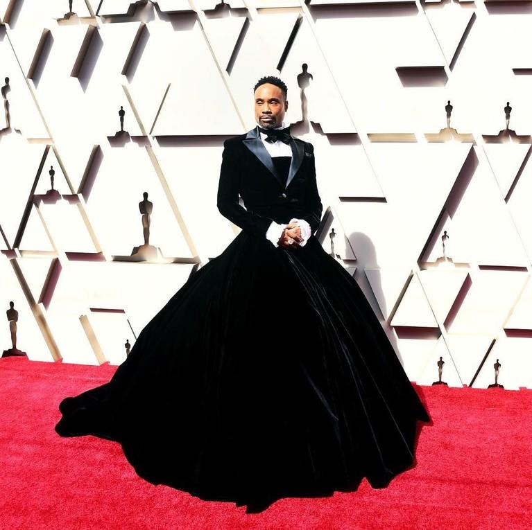 Billy Porter tampil menggunakan kostum unik perpaduanTuxedodanDressberwarna hitam. Ini adalah kostum karya desainer Christian Siriano.