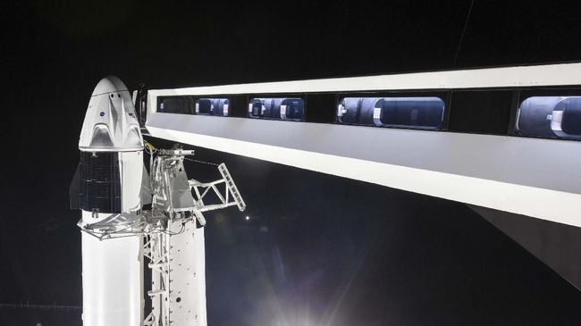 In this Jan. 3, 2019 photo, provided by SpaceX,  the crew access arm is extended to the SpaceX Crew Dragon spacecraft at NASA's Kennedy Space Center's Launch Complex 39A, in Florida. SpaceX is closing in on human spaceflight with this weekend's debut of a new capsule designed for astronauts. The six-day test flight will be real in every regard, beginning with a Florida liftoff Saturday, March 2 and a docking the next day with the International Space Station. But the Dragon capsule won't carry humans, rather a test dummy in the same white SpaceX spacesuit that astronauts will wear. (SpaceX via AP)