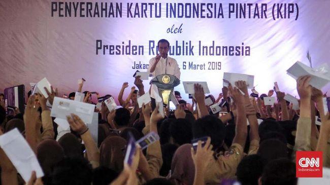 Presiden Joko Widodo membagikan Kartu Indonesia Pintar (KIP) sambil menjelaskan KIP Kuliah yang bisa digunakan siswa melanjutkan sekolah ke perguruan tinggi.