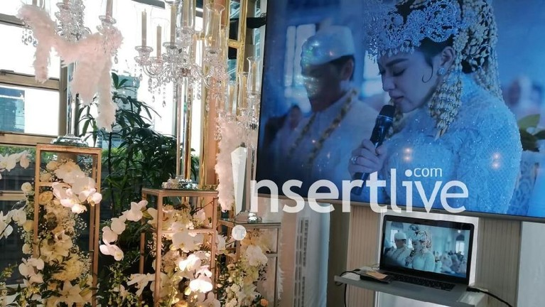 Di sudut lokasi tersebut disediakan layara televisi yang memutar prosesi pernikahan keduanya beberapa waktu lalu yang digelar di Jepang.