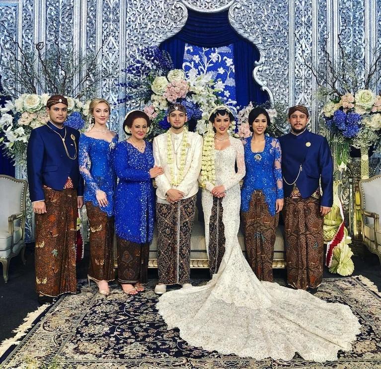 Sang kakak ipar, Varsha Strauss, juga mengunggah potret kebahagiaan pernikahan Kezia dan Adi. Tampak keluarga mempelai laki-laki kompak memakai kebaya biru.