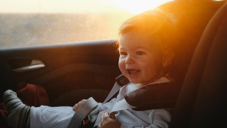 Cute baby boy driving in his car seat with a smile
