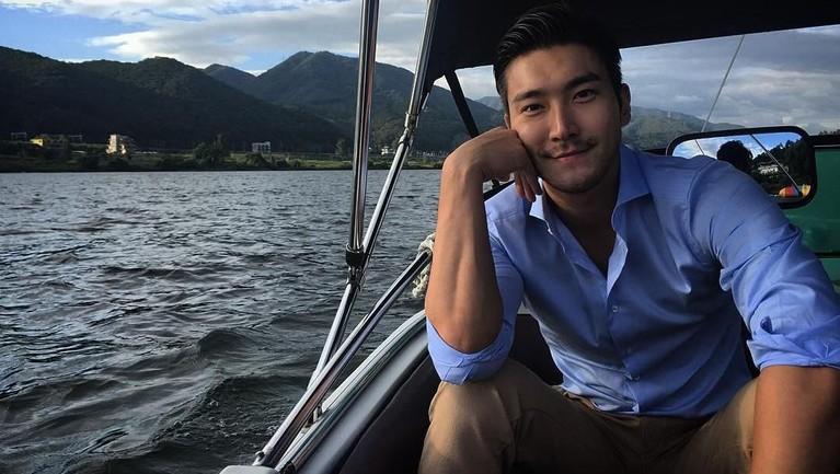 Pakai kemeja biru dengan lengan yang digulung, Siwon tersenyum manis di atas sebuah kapal. Yakin deh, Insertizen pasti kepincut sama dia kan?