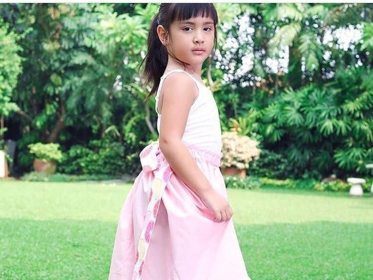 Anggunnya Mikhayla saat kenakan gaun merah muda dan putih. Anak pertama Ardi Bakrie itu juga menguncir rambutnya.
