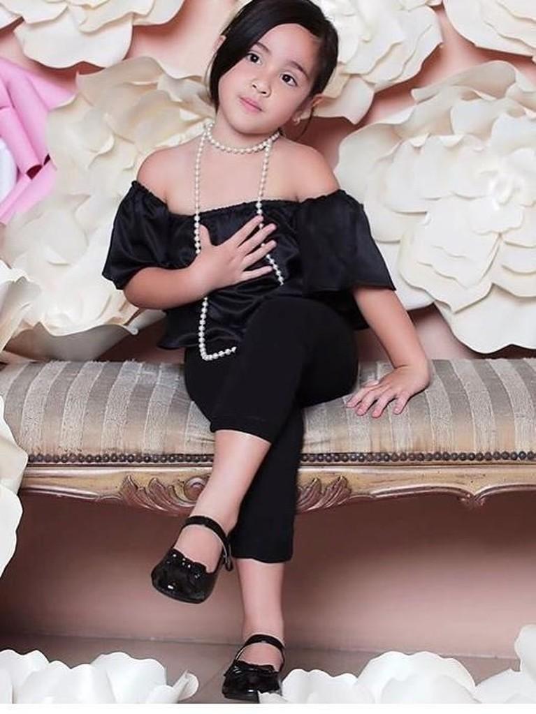 Mikhayla tampil cantik dengan outfit serba hitam. Bocah yang berhasil meraih peringkat pertama Gymnastic di Bangkok itu mengenakan off shoulder dengan perpaduan akesori kalungnya.