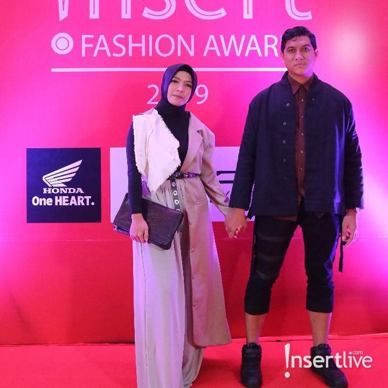 Pasangan suami istri, Tantri Kotak dan Arda Naff juga tampil memukau saat di red carpet IFA 2019. Tantri cantik dengan dress perpaduan warna hitam dan krem, sedangkan Arda tampak cooldengan outer berwarna gelap.