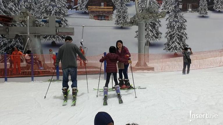 Pengunjung sedang asik bermain ski salju bersama keluarga di arena wisata Trans Snow World Juanda.