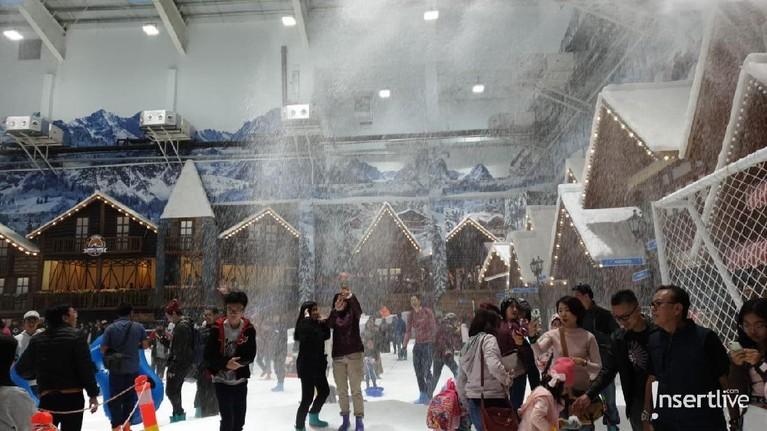 Pengunjung sedang diguyur hujan salju di arena Trans Snow World Juanda.