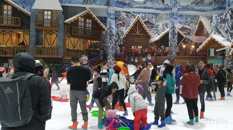 Pengunjung terlihat asik bermain salju di arena wisata Trans Snow World Juanda