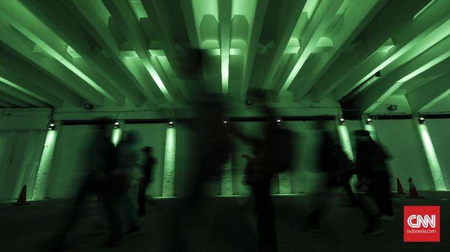 Pejalan kaki melewati pedestrian dengan lampu penerang jalan warna-warni di terowongan Jalan Kendal, Jakarta, Senin, 25 Maret 2019.  Fasilitas  ini hanya diperuntukan untuk pejalan kaki sebagai penunjang konsep Transit Oriented Development (OTD) Dukuh atas yang menghubungkan penumpang MRT, Commuter Line, Transjakarta dan Kereta Bandara. CNNIndonesia/Safir Makki