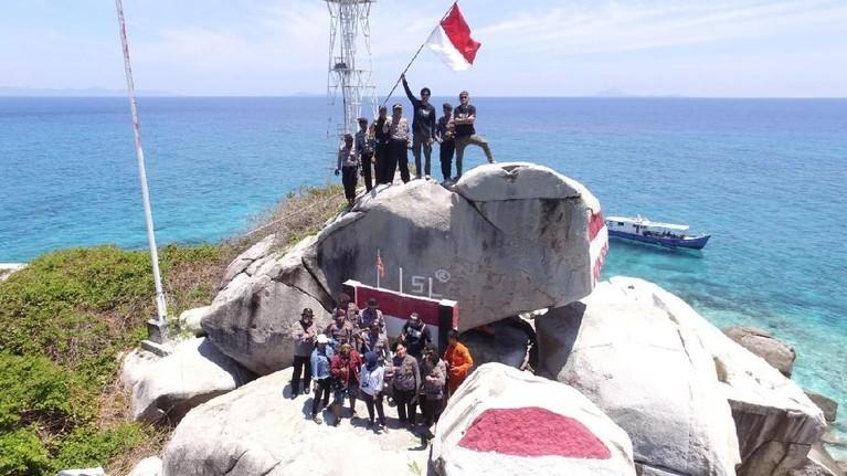 Bersama para penduduk pulau, tim MTMA tak lupa berpose dengan mengangkat benderakebangsaanIndonesia, merah putih.