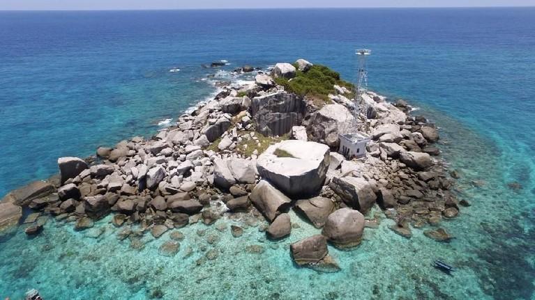 Penampakan Pulau Tokong yang memiliki tumpukan batuan dan lautan yang biru dan bening.