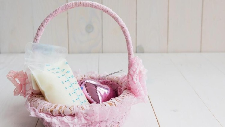 Breastmilk in Breast milk storage bag and heart toy on pink weave rattan basket with white wooden background. Nutrition food for healthy baby with copy space for text.