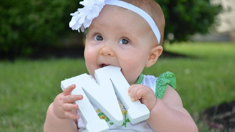 A pretty and oung infant tastes the large white wooden M while sitting in her front yard.  She is holding the letter to spell Mom.  Later she will hold the letter O and again the letter M.