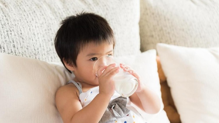Happy little asian girl hand holding drinking milk glass, sitting on sofa at home. Medicine and health care concept.
