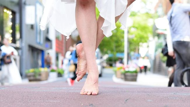 Low angle view of a dancer standing barefoot in the middle of a busy city street.