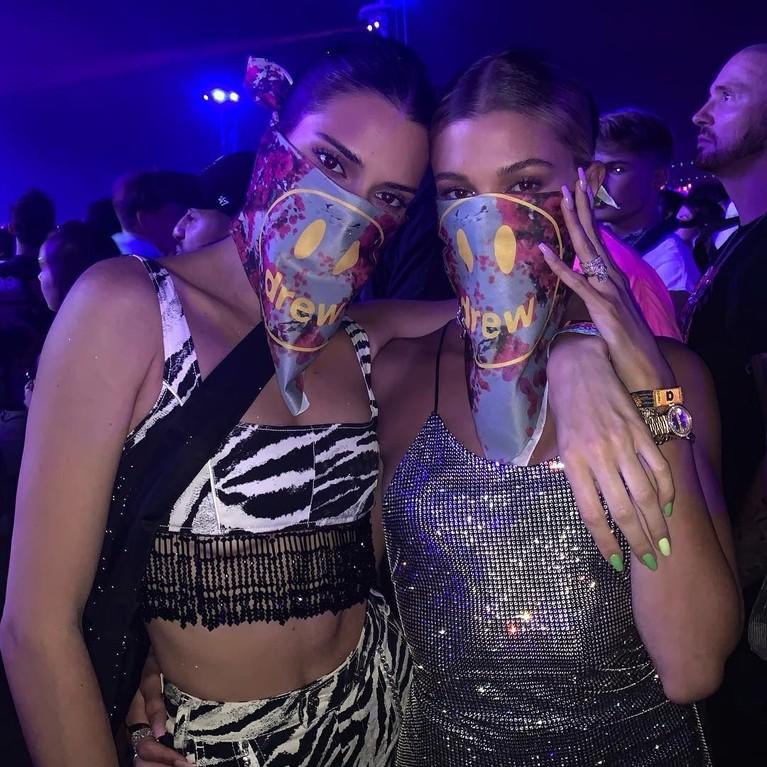 Kendall Jenner & Hailey Bieber tak ketinggalan menikmati lantunan musik di Coachella 2019. Kendall terlihat memakai crop bra top dengan motif zebra sedangkan Hailey memakai crop bra top dengan warna silver yangholographic.Mereka juga kompak memakai buff bermerek Drew, label pakaian milik suami Hailey, Justin Bieber.