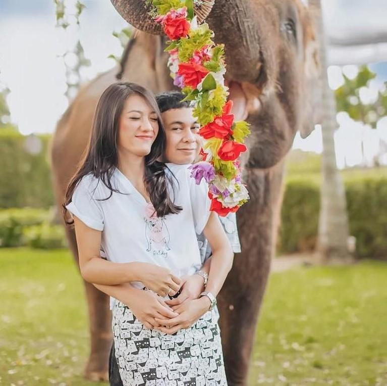 Kemesraan Raditya Dika & Anissa Aziza yang tengah berfoto dengan latar belakang gajah.