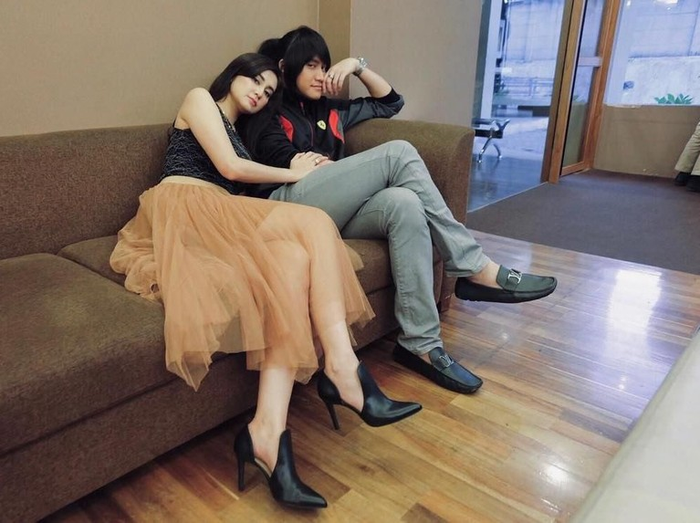 Vicy tampak menyandarkan kepanya di pundak Kevin saat keduanya sedang duduk di sebuah kursi.