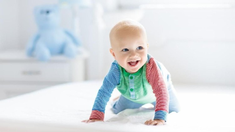 Baby boy crawling on bed. Little child playing in white sunny bedroom. Infant kid learning to crawl. Nursery for children. Textile, clothing and bedding for kids. Family morning at home.