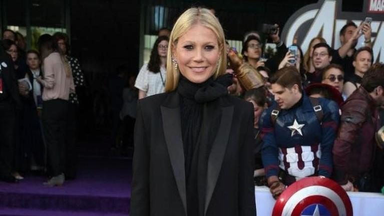 Gwyneth Paltrow tampil dengan mengenakan gaun hitam panjang yang dipadukan dengan jas dengan warna yang senada.